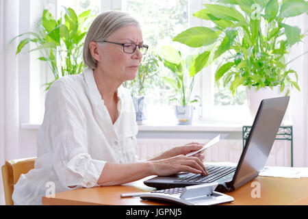 Annoyed senior woman at home with a calculator and lots of receipts in front of her laptop making her annual tax - Stock Photo
