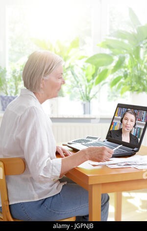 Senior woman at home with her laptop and lots of receipts, listening to an accountant before making her annual tax - Stock Photo