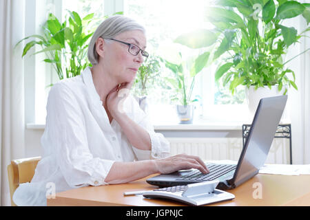 Senior woman in her living room staring annoyed at the screen of her laptop,computer or financial problems - Stock Photo