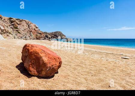 The volcanic rock colored in vivid red on sandy Paleochori Beach. Milos. Cyclades Islands, Greece. - Stock Photo