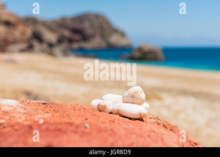 White pebles on the volcanic rocks colored in vivid red on Paleochori Beach. Cyclades Islands, Greece. - Stock Photo