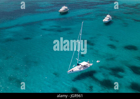 Aerial view of a sail boat and yachts on amazing beach with a turquoise and transparent sea. Emerald Coast, Sardinia, - Stock Photo