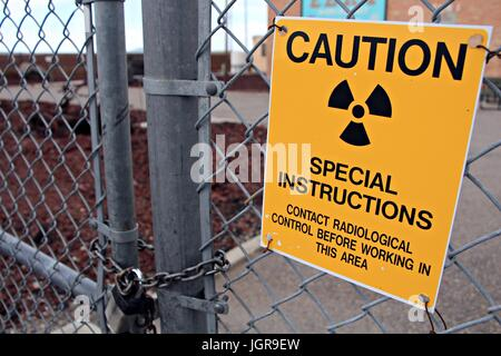 Radiological warning sign on a padlocked fence - Stock Photo