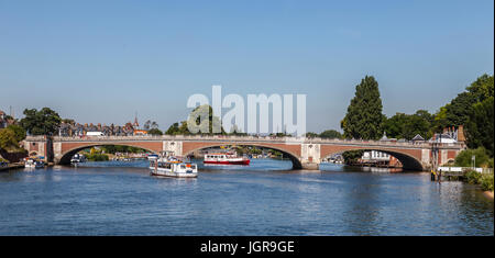 Hampton Court Bridge (1933) over the River Thames between Hampton, London and East Molesey, Surrey with busy ferry - Stock Photo