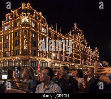 A group of tourists passing the illuminated Harrods Department Store in Knightsbridge, London, during a night open - Stock Photo