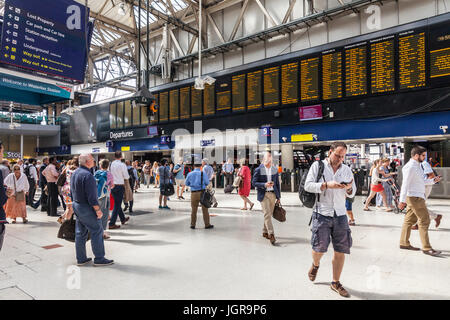 Passengers, concourse, arrivals and departures board and directional signs in Waterloo Station, a large railway - Stock Photo