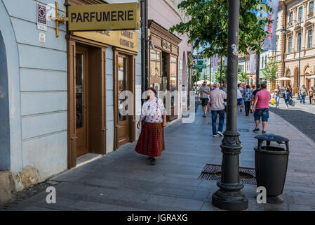 Old woman weraing traditional dress on Nicolae Balcescu Street in Historic Center of Sibiu city of Transylvania - Stock Photo