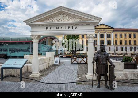 Roman legionary bronze statue in next to Roman ruins in Alba Carolina Fortress in Alba Iulia city located in Alba - Stock Photo