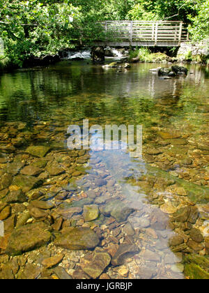Small river running under a bridge with water so clear you can see the rocks on the river bed, The Lake District, - Stock Photo