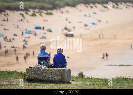 Two elderly holidaymakers sitting on a rock on the Headland overlooking Fistral Beach in Newquay, Cornwall. - Stock Photo