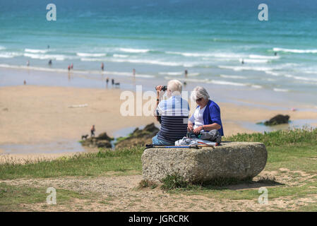 Elderly holidaymakers sitting on a rock on the Headland overlooking Fistral Beach in Newquay, Cornwall. - Stock Photo