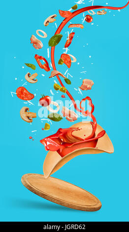 Tasty pizza and falling ingredients on blue background - Stock Photo