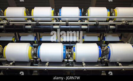 Textile fabric manufacturing machines in work. - Stock Photo