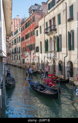 VENICE, ITALY - JULY 1, 2016: Gondoliers navigate gondolas through a canal in Venice, Italy. - Stock Photo