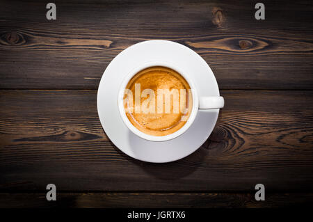 Overhead view of a freshly brewed mug of espresso coffee on rustic wooden background with woodgrain texture - Stock Photo