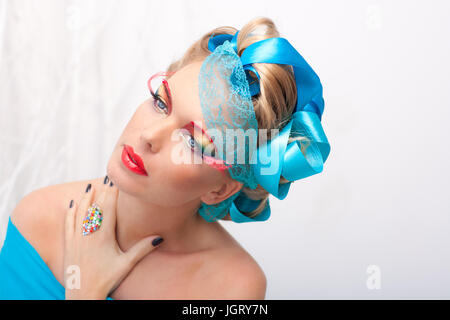 Studio photograph of a beautiful young woman with blond hair decorated with blue ribbons. With artistic colorful - Stock Photo
