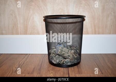 black mesh trash can half filled with American money, dollar bills with a hardwood floor background, white base - Stock Photo