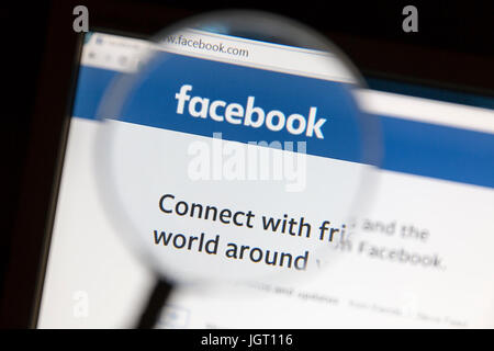 Facebook website under a magnifying glass. Facebook is the most visited social network in the world - Stock Photo
