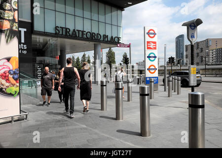 People walking outside Stratford train station at Stratford Place with transportation rail and underground tube - Stock Photo