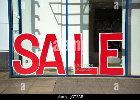 Large red 'For Sale' sign in a shop window - made of large red letters - Stock Photo