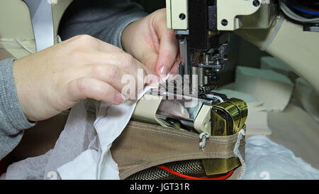 Close up portrait of hands of seamstress sewing using industrial sewing machine. Stocking manufacturing in a factory. - Stock Photo