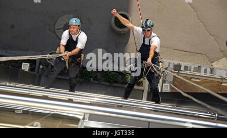 Workers hanging on climbing ropes, showing raised fist sign. - Stock Photo