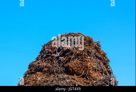 A pile of garbage on blue sky background. Metal debris on a solid blue background. - Stock Photo