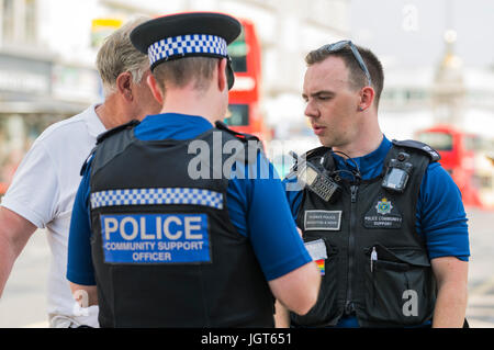 PCSOs (Police Community Support Officers) speaking to someone on the streets of Brighton, East Sussex, England, UK.