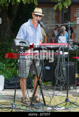 Man in a music band standing outside playing the keyboard. - Stock Photo