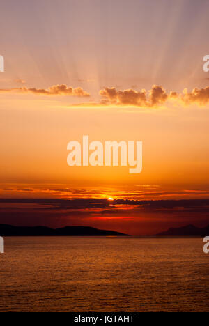 vertical image of golden sunset with sun centrally low above the sea and sunrays coming through clouds above, with - Stock Photo