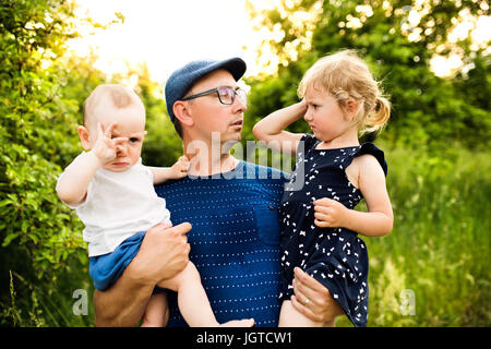 Young father with little children in sunny summer nature - Stock Photo