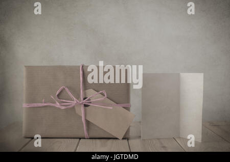 Photograph with vintage treatment of a gift box wrapped in brown paper, tied to a bow with with pale pink raffia - Stock Photo