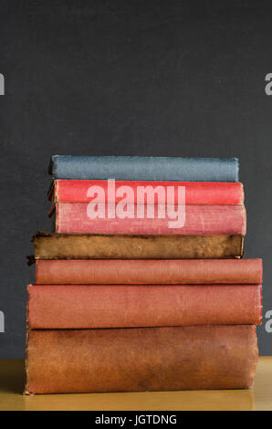 Close shot of a pile of old, shabby, well used text books stacked in a pile on a desk in front of a black chalkboard. - Stock Photo
