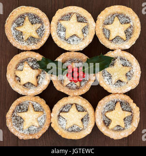 Homemade christmas mince pies with pastry stars and icing sugar dusting, holly and red berries on oak wood background. - Stock Photo
