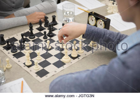 Close up middle school students playing chess in chess club - Stock Photo