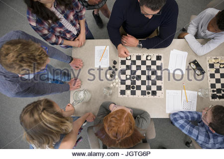 Teacher and middle school students playing chess in chess club - Stock Photo