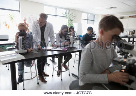 Teacher helping middle school students using microscopes, conducting scientific experiment in science laboratory - Stock Photo
