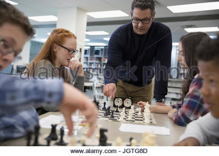 Teacher helping middle school students playing chess in chess club - Stock Photo