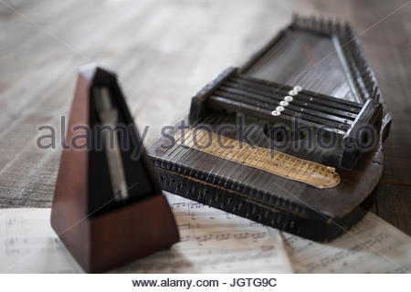 Still life vintage metronome and zither on sheet music - Stock Photo