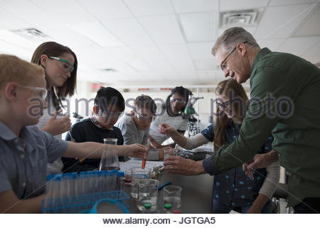 Teacher and middle school students conducting scientific experiment in science laboratory - Stock Photo