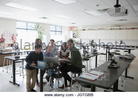 Teacher and middle school students conducting scientific experiment at laptop in science laboratory - Stock Photo