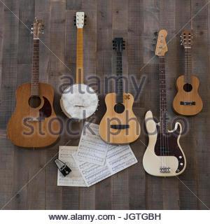 Knolling of guitars, banjo and ukulele on sheet music - Stock Photo