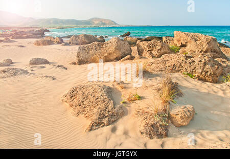 Falasarna beach at sunrise with rocks and plants at foreground and mountains at background on clear summer day, - Stock Photo
