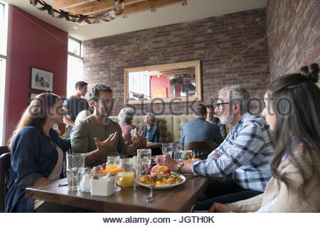 Multi-generation family talking and eating brunch at diner table - Stock Photo