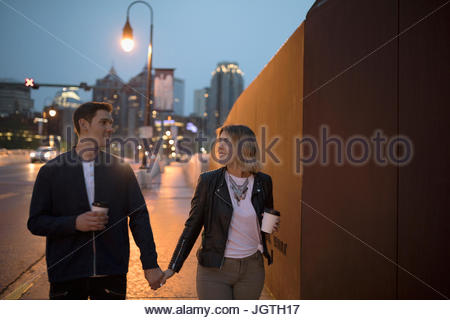 Young couple walking with coffee along urban sidewalk at dusk - Stock Photo
