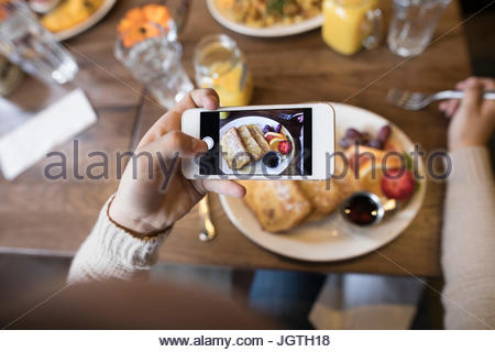 Personal perspective teenage girl photographing brunch food with camera phone - Stock Photo
