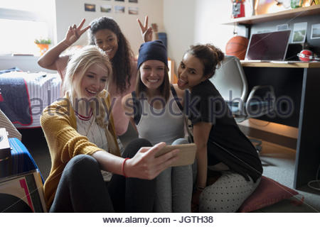 Playful female college student friends taking selfie in dorm room - Stock Photo