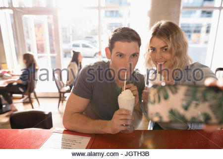 Young couple drinking milkshakes, taking selfie with camera phone - Stock Photo