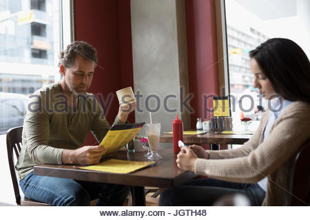 Father looking at menu and daughter using cell phone at diner table - Stock Photo