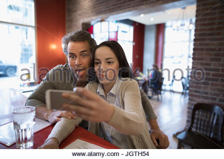 Father and teenage daughter taking selfie at diner counter - Stock Photo